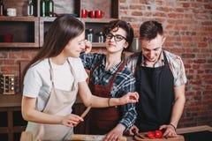 Amis ayant l'amusement tout en préparant le dîner Image libre de droits
