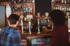 Amis ayant la bière au compteur de barre Photos libres de droits