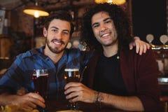 Amis ayant la bière au compteur de barre Photographie stock libre de droits