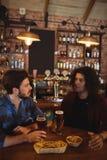 Amis ayant la bière dans le bar Image stock