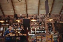Amis ayant la bière dans le bar Photographie stock