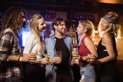 Amis ayant la boisson au compteur dans la boîte de nuit Photo libre de droits
