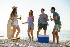 Amis ayant la boisson tout en dansant sur le rivage à la plage Photographie stock libre de droits