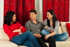 Amis ayant la conversation sur le sofa Image stock