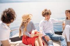 Amis ayant la navigation d'amusement sur un yacht la mer, en riant, la causerie et le refroidissement Photos libres de droits