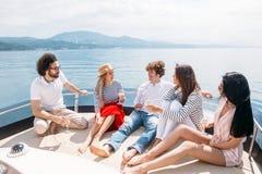 Amis ayant la navigation d'amusement sur un yacht la mer, en riant, la causerie et le refroidissement Image libre de droits