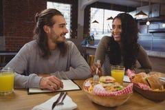 Amis ayant la nourriture en café Image libre de droits