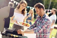 Amis ayant la partie de barbecue dans l'arrière-cour Photo stock