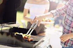 Amis ayant la partie de barbecue dans l'arrière-cour Photos libres de droits