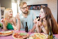 Amis ayant la partie de pizza à la maison Image libre de droits