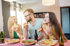 Amis ayant la partie de pizza à la maison Photos libres de droits
