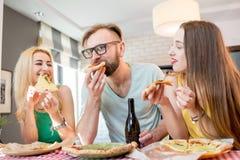 Amis ayant la partie de pizza à la maison Image stock