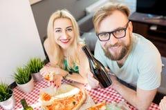Amis ayant la partie de pizza à la maison Images stock