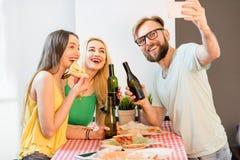 Amis ayant la partie de pizza à la maison Images libres de droits
