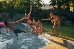 Amis ayant la partie de vacances d'été au poolside Images stock