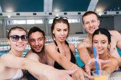 Amis ayant la partie et buvant des seaux à une piscine Image libre de droits