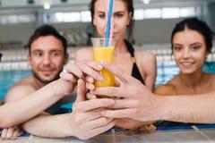 Amis ayant la partie et buvant des seaux à une piscine Image stock