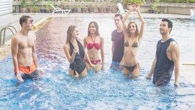 Amis ayant la partie et dansant dans une piscine - mode de Photo libre de droits
