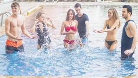 Amis ayant la partie et dansant dans une piscine - mode de Photographie stock