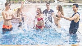 Amis ayant la partie et dansant dans une piscine - mode de Photos stock