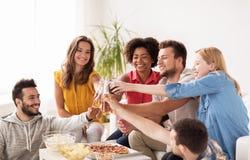 Amis ayant la partie et faisant tinter des boissons à la maison Images stock