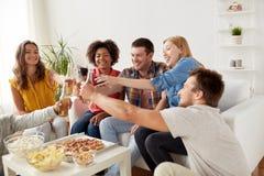 Amis ayant la partie et faisant tinter des boissons à la maison Photo libre de droits