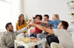 Amis ayant la partie et faisant tinter des boissons à la maison Photographie stock libre de droits