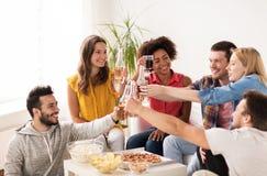 Amis ayant la partie et faisant tinter des boissons à la maison Images libres de droits