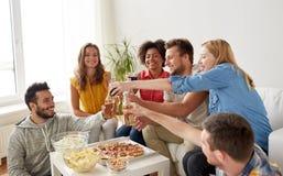 Amis ayant la partie et faisant tinter des boissons à la maison Photo stock