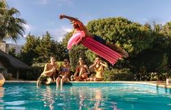 Amis ayant la partie par la piscine Image libre de droits