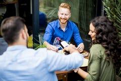 Amis ayant la réception en plein air extérieure et buvant du vin rouge Image libre de droits