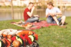 Amis ayant le barbecue extérieur Gril avec le divers barbecue, foyer sélectif Photographie stock