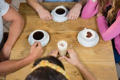 Amis ayant le café à la table Images libres de droits