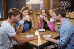 Amis ayant le café à la table Image libre de droits