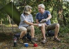 Amis ayant le café à un terrain de camping Photo stock