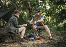 Amis ayant le café à un terrain de camping Photographie stock