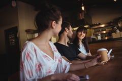 Amis ayant le café au restaurant Photographie stock libre de droits