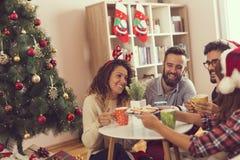 Amis ayant le café de matin de Noël Photographie stock