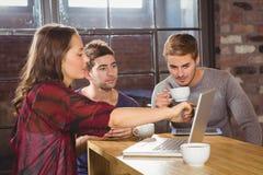 Amis ayant le café et à l'aide de l'ordinateur portable ensemble Image stock