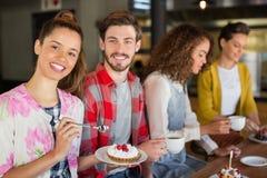 Amis ayant le café et le dessert en café Photographie stock libre de droits