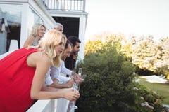 Amis ayant le champagne dans le balcon Images libres de droits