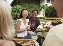 Amis ayant le dîner et les boissons dans le jardin Image stock