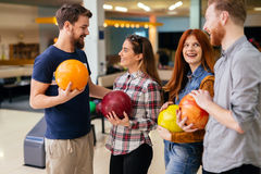 Amis ayant le grand temps jouant le bowling Image libre de droits