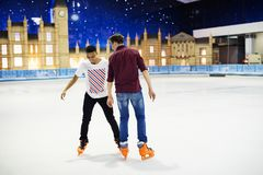 Amis ayant le patinage de glace d'amusement sur la patinoire ensemble Photo libre de droits