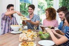 Amis ayant le repas à la table dans la maison Photo libre de droits