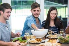 Amis ayant le repas à la table dans la maison Images libres de droits