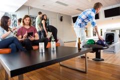 Amis ayant le temps libre dans le club de bowling Image stock