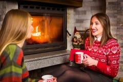 Amis ayant le thé et appréciant par la cheminée Photos stock