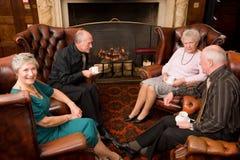 Amis ayant le thé par l'incendie Photos libres de droits