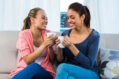Amis ayant le thé sur le sofa Photographie stock libre de droits
